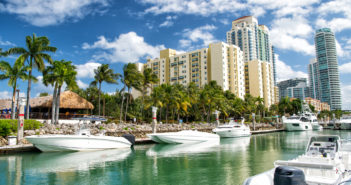 hotel buildings with yachts and palm trees © photosvit/GettyImages
