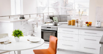 Modern kitchen interior of studio apartment with large counter and white round table © belchonock/DepositPhotos