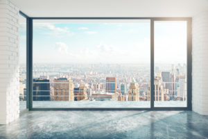 Empty loft style room with concrete floor and city view © peshkov/GettyImages