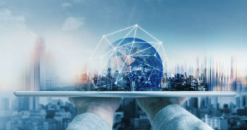 Hand holding digital tablet with global network connection technology and modern buildings. Element of this image are furnished by NASA © SasinParaksa/GettyImages